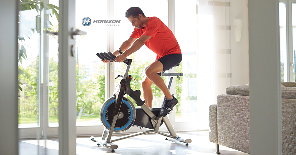 Man on Horizon Fitness exercise bike in his home.
